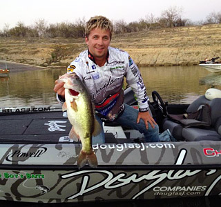 Chad Pipkens in his Douglas J-wrapped boat with a big largemouth bass caught during 2013 practice at Falcon Lake